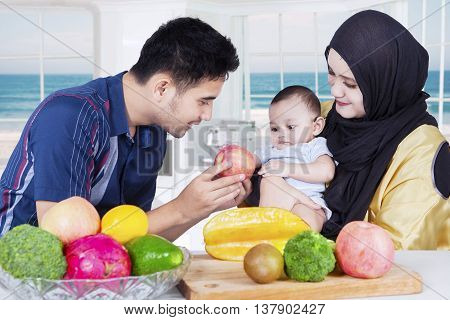 Portrait of two parents sitting in the kitchen with their little son and fresh fruit on the table