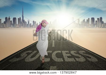 Portrait of middle eastern businessman running on the street with Success word and wearing islamic clothes
