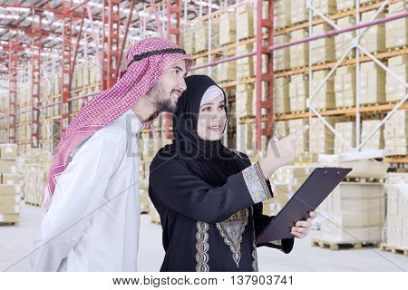 Portrait of two Arabian businesspeople wearing islamic clothes while look at the storehouse