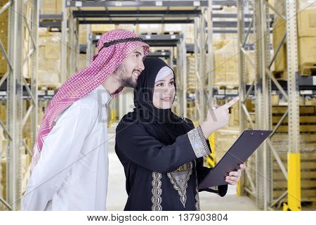 Picture of two Arabian workers look at the warehouse while wearing traditional clothes