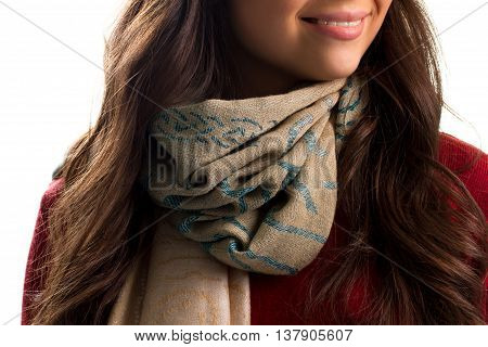 Beige scarf on woman's neck. Red garment and printed scarf. Trendy accessory for autumn outfit. Textile of top quality.