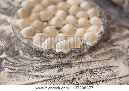 Raw homemade russian food - dumpling. Their in flower and have traditional form. Placed on the plate. Pork chicken mincemeat. Background table in kitchen.