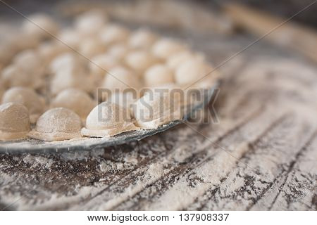 Raw homemade russian food - dumpling. They're in flour and have traditional form. Placed on the plate. Pork chicken mincemeat. Background table in kitchen. Wooden plunge.