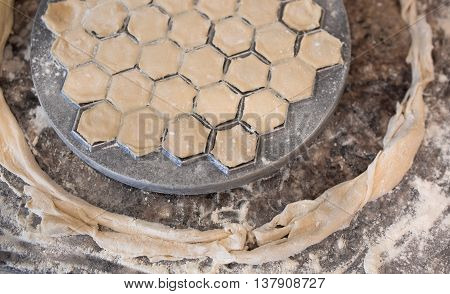 Prepare raw homemade russian food - dumpling in metal strainer pelmennica. Their in flower and have traditional form. Pork chicken mincemeat. Background table in kitchen.
