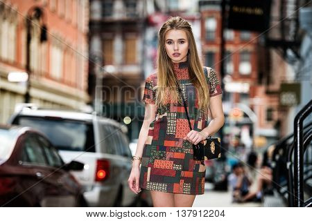 Beautiful fashionable model girl walking on New York City street wearing short elegant dress with black bag