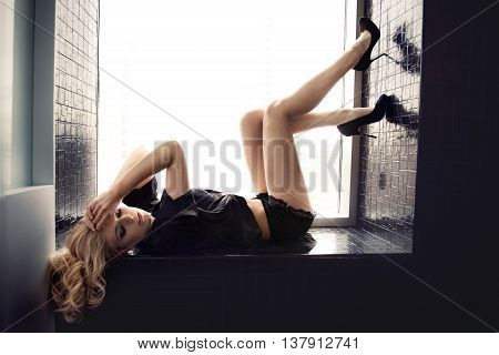 Fashion photo of beautiful blonde sexy girl lying in the shower near the window