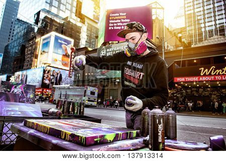 NEW YORK CITY USA - MARCH 23: graffiti artist Fobnart works on his creation for the public on Time Square on March 23 2016 in New York City USA.