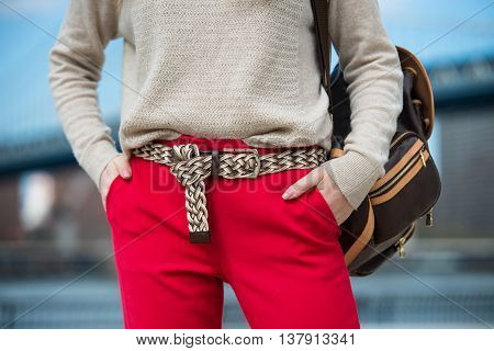Fashionable women`s casual spring outfit with red pants cardigan modern belt and shoulder bag