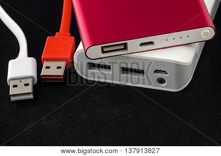 Red and white power bank with usb cable on black leather background.