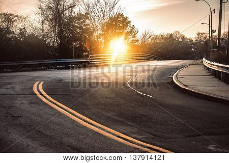 Dark asphalt road with bright yellow lines curves under sunset in smal town