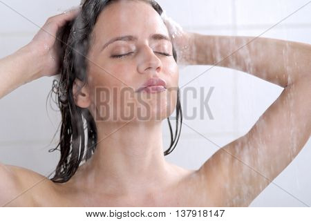 Young woman washing head with shampoo in bathroom