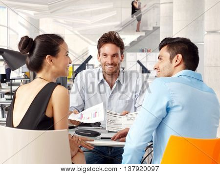 Happy young businessteam sitting at table, working together, smiling.