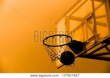 Basketball in a net silhouette. Basketball with sunset silhouette background