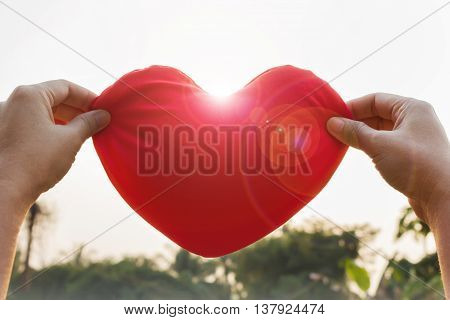 Romantic lovely valentine concept with hand gently raise up red heart with sunlight lens flare love and care concept poster