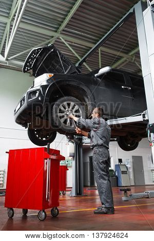 Male mechanic fixing wheel on raised SUV car in garage. Young man in mechanic uniform works with wheel of raised on lift car in auto service station. Mechanic doing service maintenance for SUV