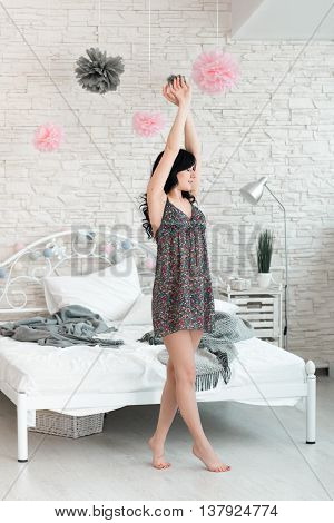 Young brunette female doing morning exercises in bedroom. Beautiful woman stretching near bed to awake. Full length image of slim young awaking woman