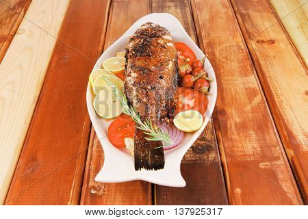 main course: whole fried seabass served on wood with lemons,tomatoes and peppers