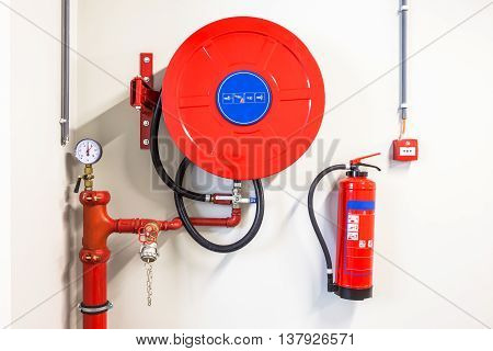an fire hose hanging on the wall and powder extinguisher