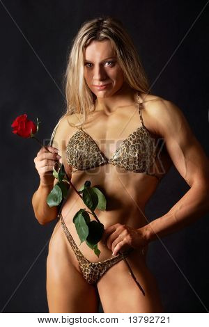 Portrait of a woman bodybuilder in bikini holding a rose poster