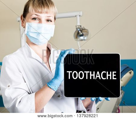 technology, internet and networking in medicine concept - femail dentist holding a tablet pc with toothache sign. at the dental equipment background.