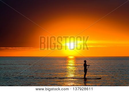 silhouette of a man paddle surfing at Henely Beach South Australia