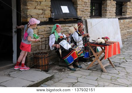 ETAR BULGARIA - JUNE 19 2016: A little Caucasian girl looks at two aged Bulgarian women who spin and knit outside the house