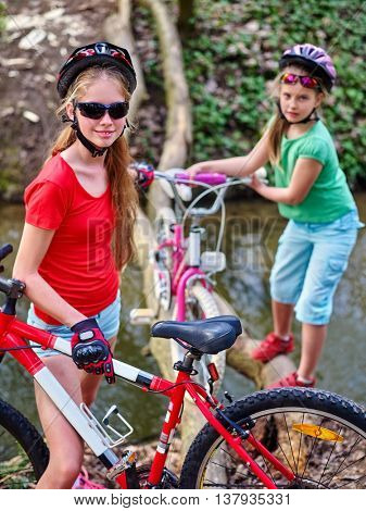 Bikes cycling girl. Girl rides bicycle. Girl cycling fording throught water on log. Cycling trip is good for health. Cyclist watch your step.