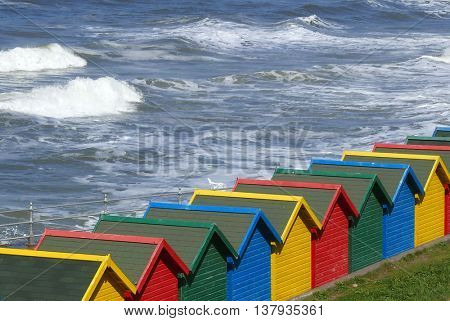 Row of colorful beach huts at Whitby, North Yorkshire, UK.