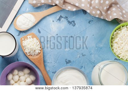 Dairy products on stone table. Sour cream, milk, cheese, yogurt and curd. Top view with copy space