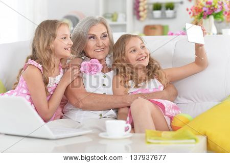 Old woman with tweenie   girls doing selfie at home
