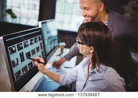 Female photo editor discussing over computer with male colleague in creative office