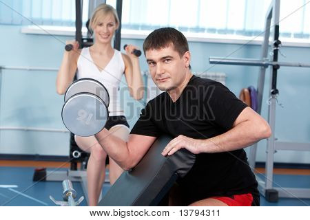 A man lifting a barbell with a woman training on exercise machine in the background