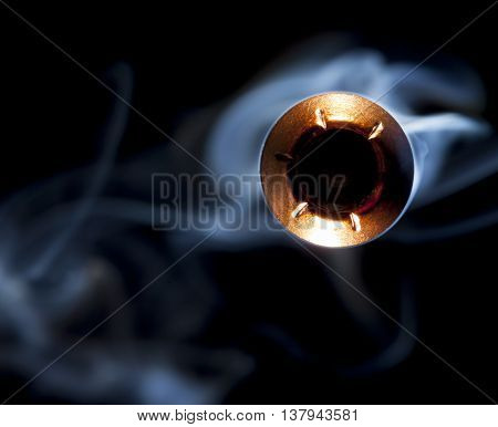One hollow point bullet and smoke heading to the camera