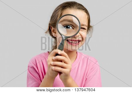 Cute little girl looking through a magnifying glass