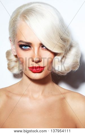 Portrait of young beautiful blonde tanned woman with stylish vintage hairdo and matte red lipstick