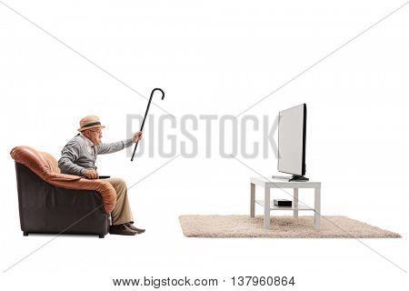 Angry senior watching television and threatening with his cane towards the TV isolated on white background