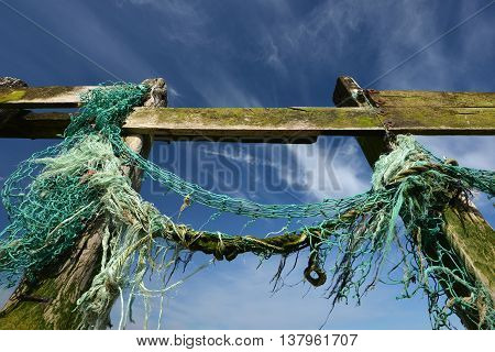 Old fishing nets caught up on wooden groynes