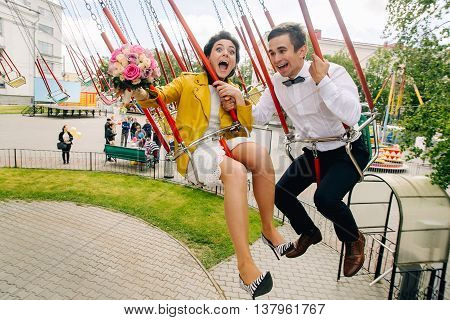 Emotional newlyweds laughing while riding on high carousel in amusement park. Expressive wedding couple at carnival