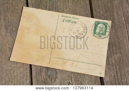 old blank vintage postcard with old stamp is on old wood