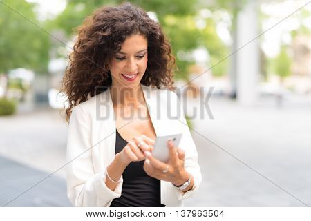 Smiling woman using her mobile phone while walking in a city