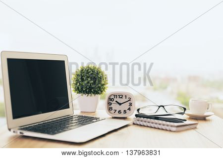 Side view of wooden office desktop with blank laptop plant clock glasses stationery items and coffee cup on blurry background. Mock up
