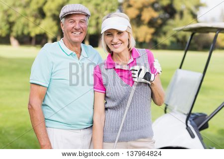 Portrait of happy mature couple standing at golf course