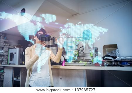 Digitally generated image of world map against female graphic designer using the virtual reality headset