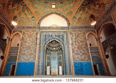 YAZD, IRAN - OCT 19, 2014: Empty space of ancient mosque with artistic tiles and ceilings on October 19, 2014. With population of 270.600 families Yazd is centre of Persian architecture
