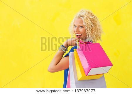 Woman holding swhopping bags over her shoulder