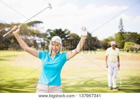 Portrait of cheerful golfer woman with arms raised while standing on field