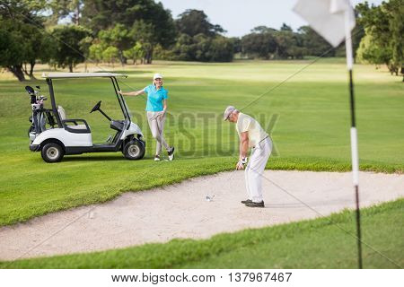 Golfer playing on sand trap by woman at golf course
