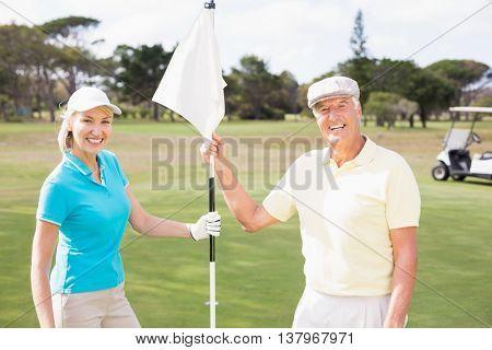 Portrait of smiling golfer couple holding white flag