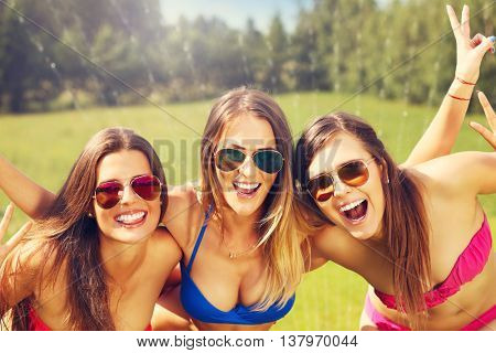 Picture presenting a group of women in bikin having fun outdoors