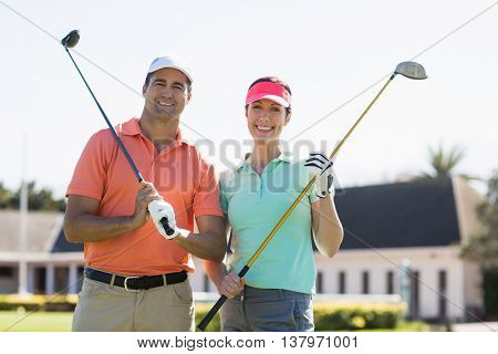 Portrait of smiling couple holding golf clubs while standing on field